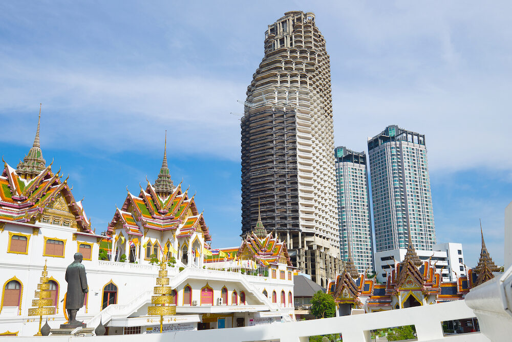 BANGKOK, THAILAND - : View of the abandoned skyscraper of Sathorn Unique Tower from the Buddhist temple Wat Yannava