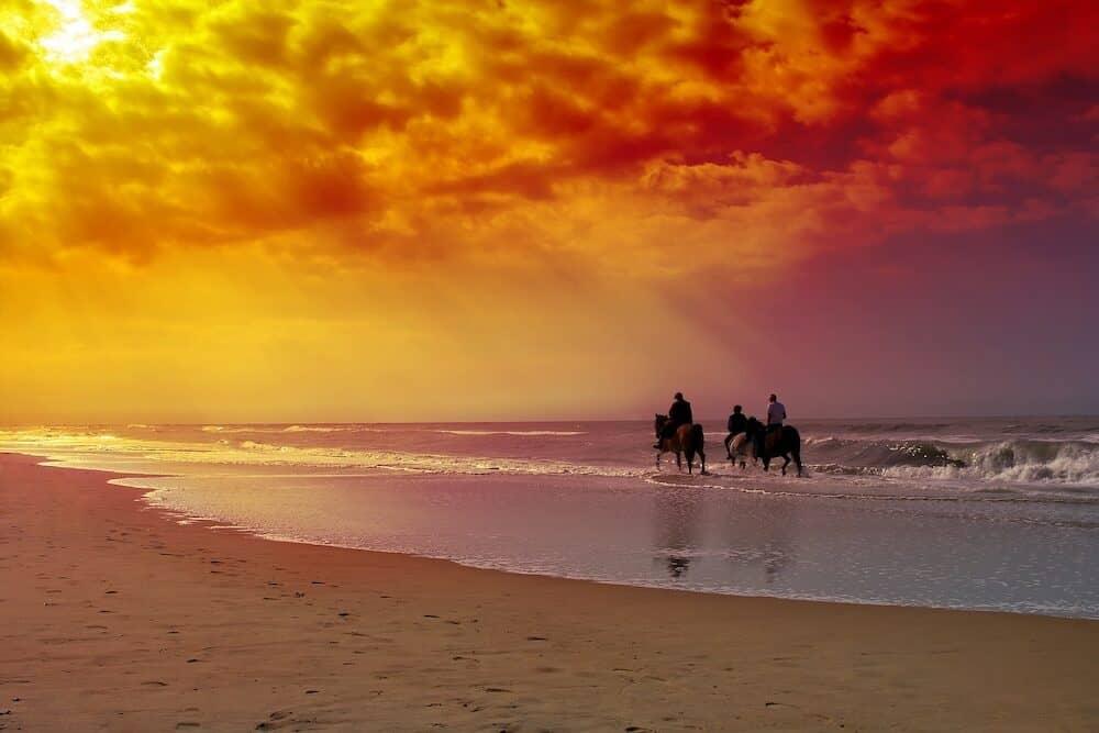 Three horse riders on the beach.