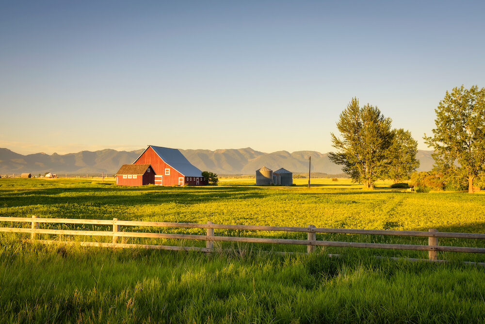 Summer sunset with a red barn and silos in rural Montana with Rocky Mountains in the background.