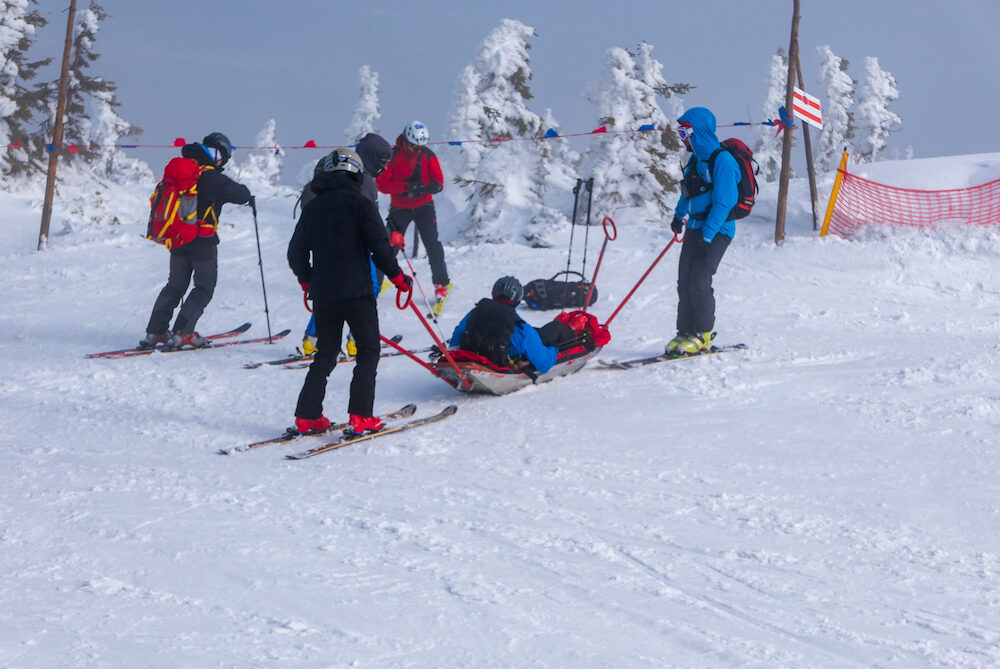 Ski rescue team with slide stretcher, brings help to ski during bad weather conditions.