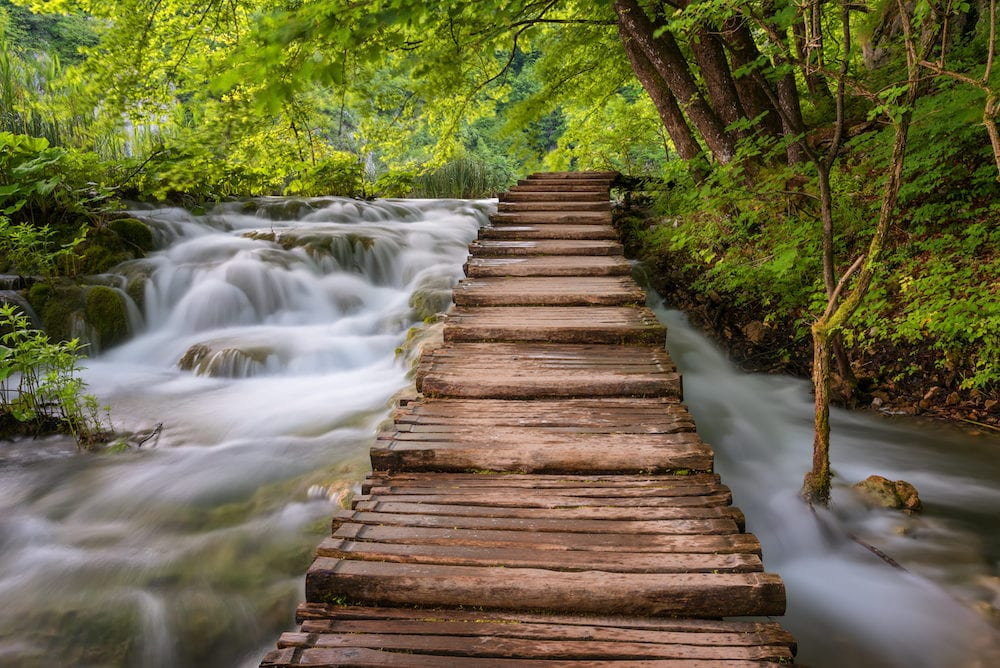 Plitvice Lakes National Park in Croatia.Beautiful view of waterfalls with turquoise water and wooden pathway through over water. Plitvice Lakes National Park, Croatia. Famous attraction, summer landscape.