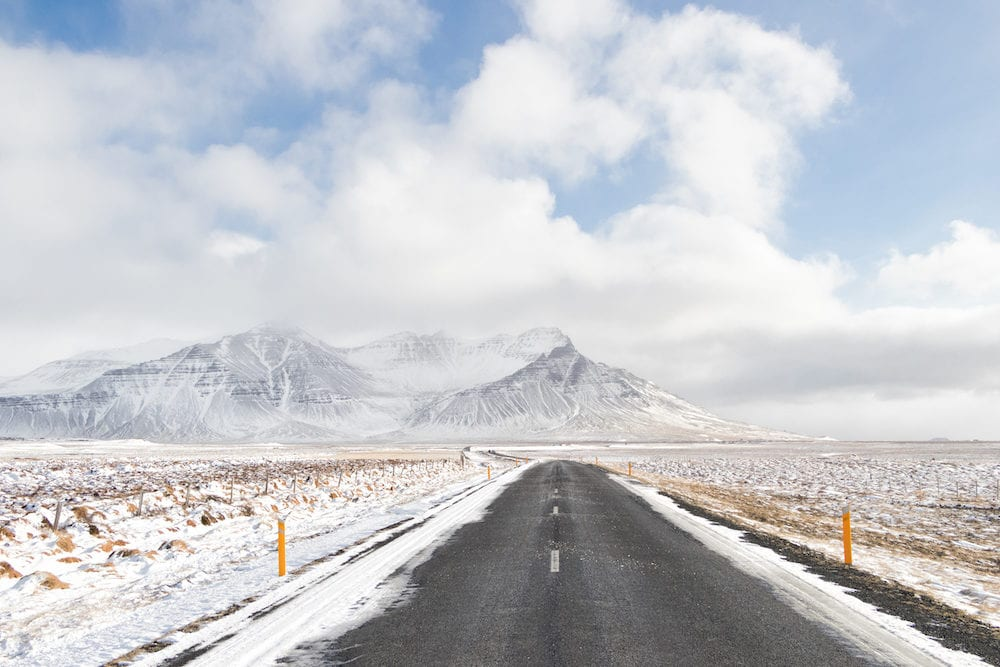 landscape of Iceland's golden circle road in winter.Asphalt road go straight to snow capped mountains.empty highway in countryside of iceland with volcano in background