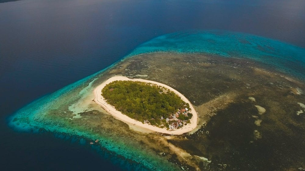 Aerial view of beautiful tropical island Mantigue with white sand beach, Camiguin. Beautiful sky, sea, resort. Seascape: Ocean and beautiful beach paradise. Philippines. Travel concept.