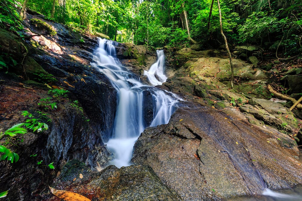 Kathu waterfall in a tropical forest at sunny day. Phuket Thailand