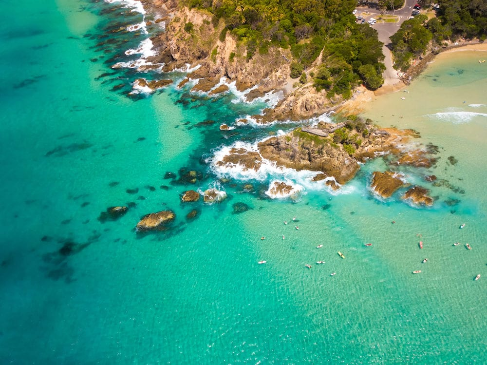 An aerial view of Byron Bay on a clear day with blue water