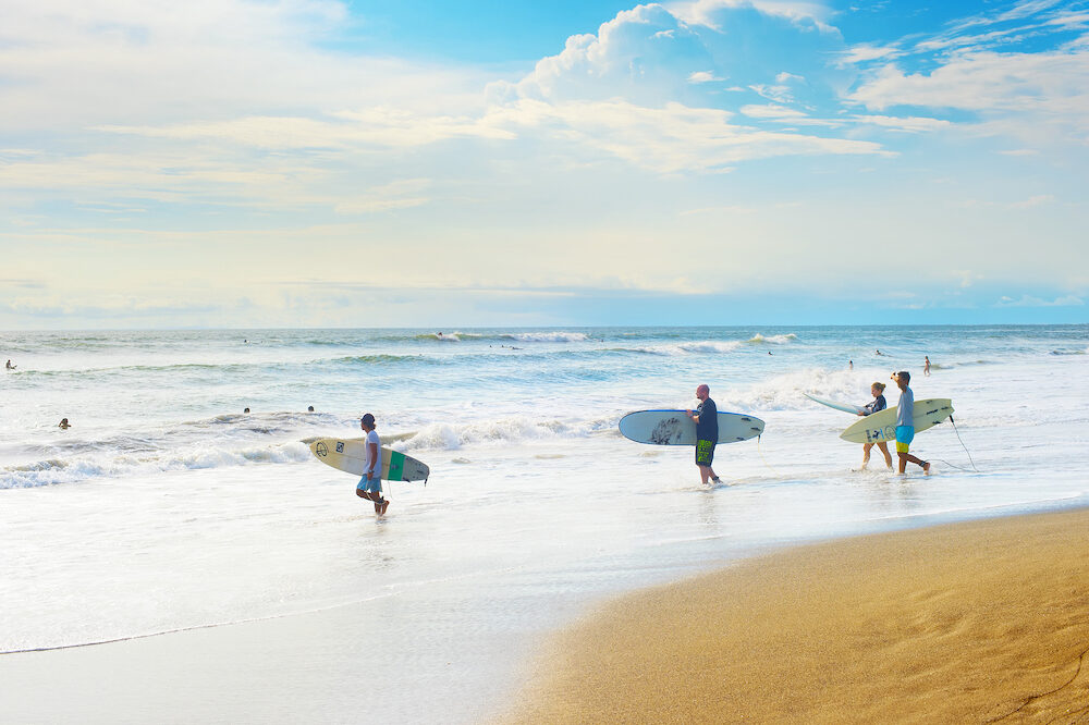 CANGGU BALI ISLAND INDONESIA - Group of surfers going to surf on the beach. Bali island is one of the worlds best surfing destinations