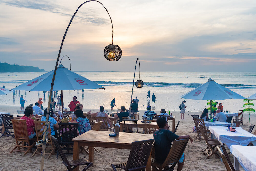 Bali Indonesia - Jimbaran tropical beach is a main popular balinese attraction famous for the clear aqua blue water and sea food restaurants in Bali Indonesia.