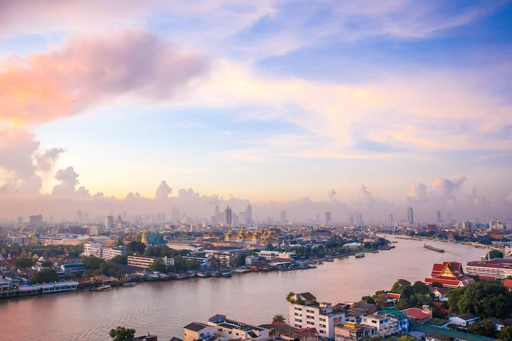 Sun rise The Chao Phraya River Behind the view of the royal palace in the corner.