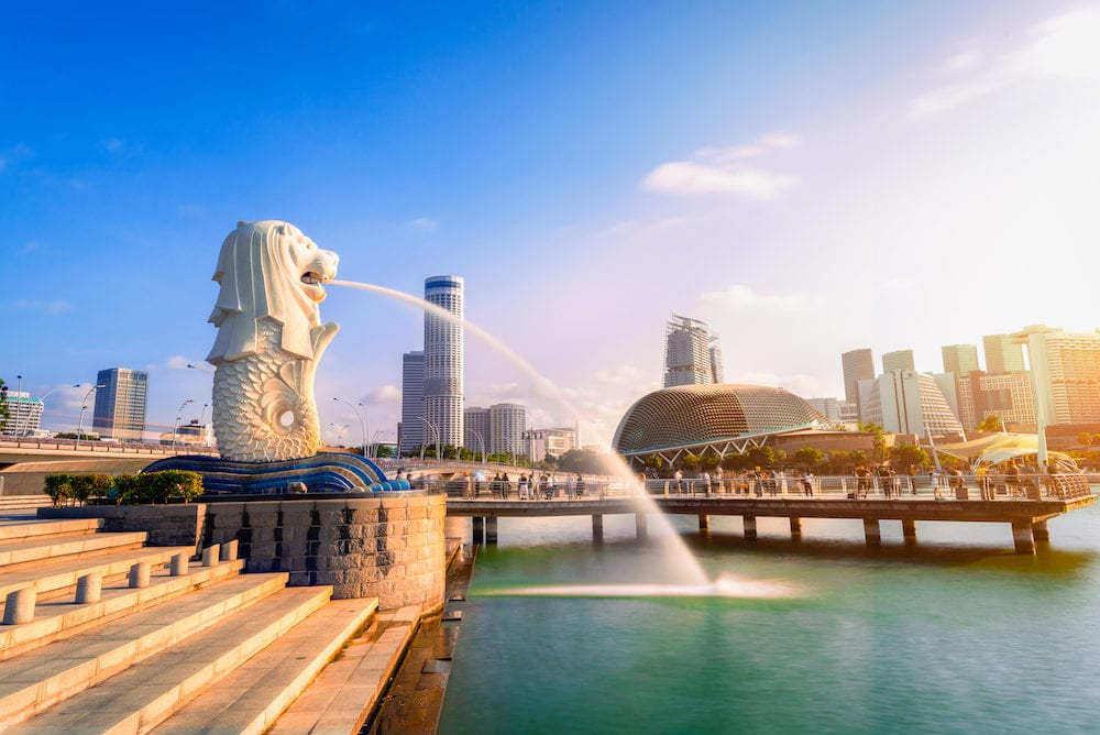 SINGAPORE-: Merlion statue fountain in Merlion Park and Singapore city skyline at sunrise. Merlion fountain is one of the most famous tourist attraction in Singapore.