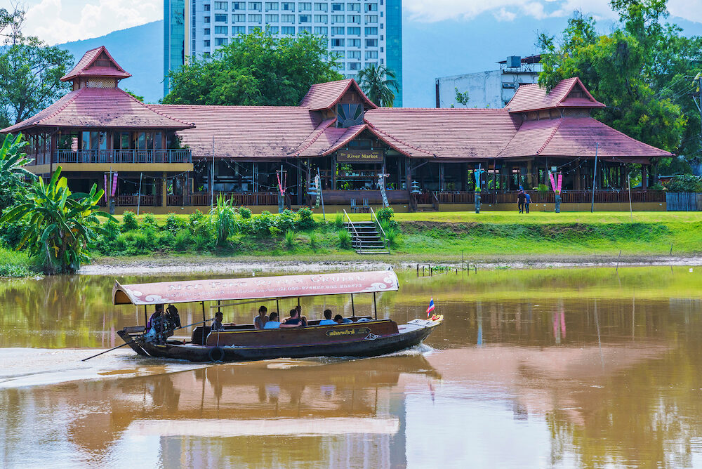CHIANG MAI THAILAND - This is a view of a tourboat and riverside buildings along the famous Ping river in Chiang Mai