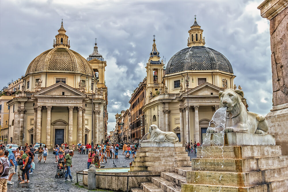 Rome/Italy -Fountains around the Egyptian Obelisk and Churches of Santa Maria dei Miracoli and Santa Maria di Montesantom in Piazza del Popolo on a cloudy day
