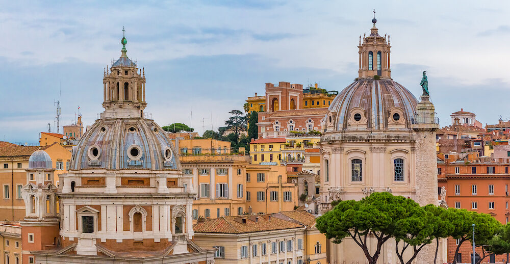 View onto rooftops of Rome skyline with domes of 16th-century church Santa Maria di Loreto across from the Trajan's Column near the Monument of Vittorio Emanuele at Piazza Venezia in Rome Italy
