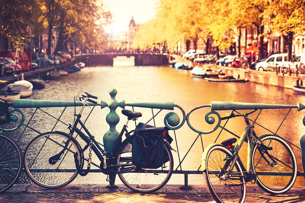 Bikes on the bridge in Amsterdam Netherlands Europe. Amsterdam canal scene with bicycles and bridges. Photo toning at retro color. Spring or autumn time in the city. Travel Europe.