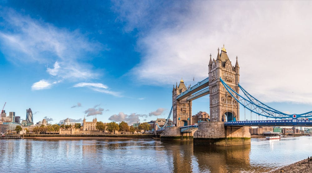 Panoramic London skyline with iconic symbol, the Tower Bridge and Her Majesty's Royal Palace and Fortress, known as the Tower of London as viewed from South Bank of River Thames in the morning light