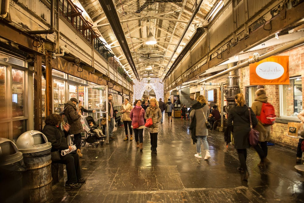 People on shopping at Chelsea Market. It is an enclosed urban food court shopping mall office building and television production facility in New York City USA