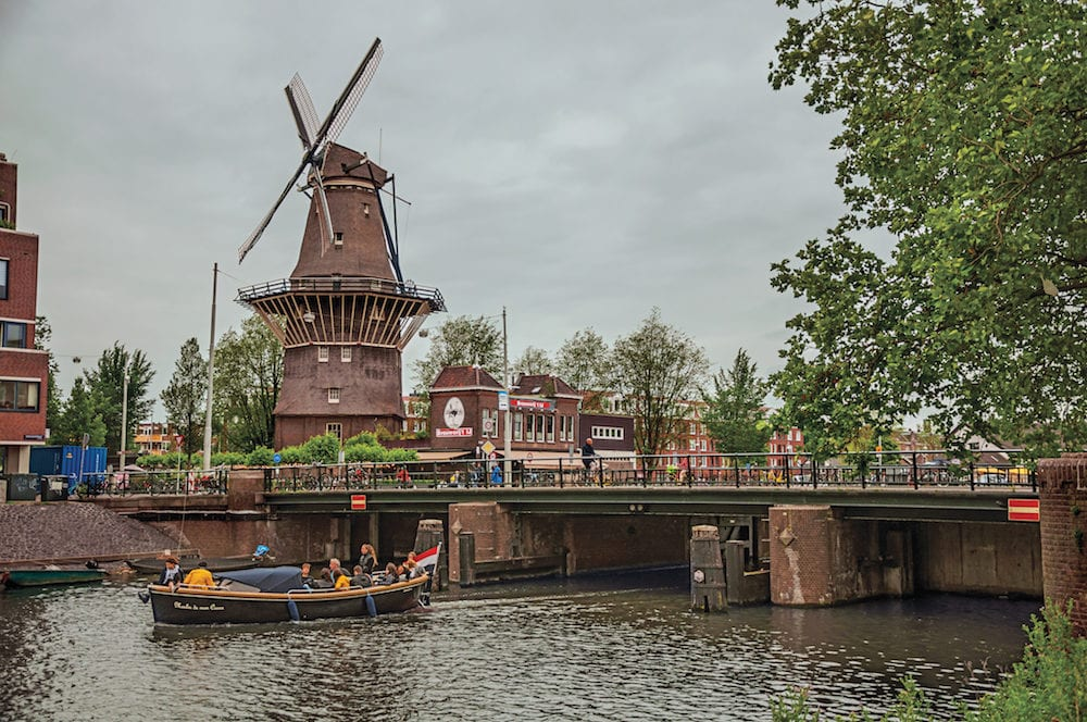 Amsterdam, northern Netherlands - Bridge over canal, trees and old windmill on the bank with cloudy sky in Amsterdam. Famous for its huge cultural activity, graceful canals and bridges.