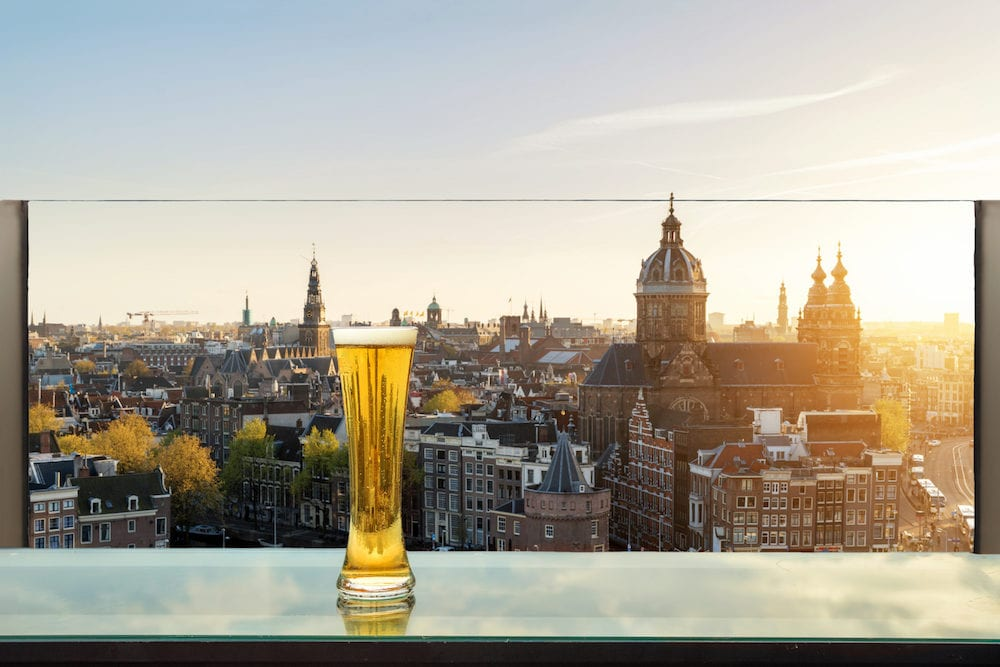 Beer and foam beer on table in rooftop bar with Amsterdam skyline in background in Amsterdam Netherlands. Viewpoint of Amsterdam Netherlands.