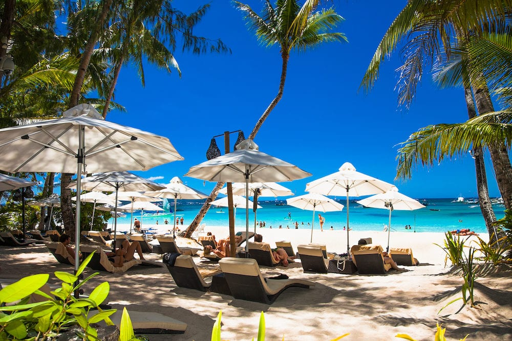 BORACAY, PHILIPHINES-Tropical vacation on white sand beach with sun, blue sky and palm trees. White beach at Boracay island Philiphines.