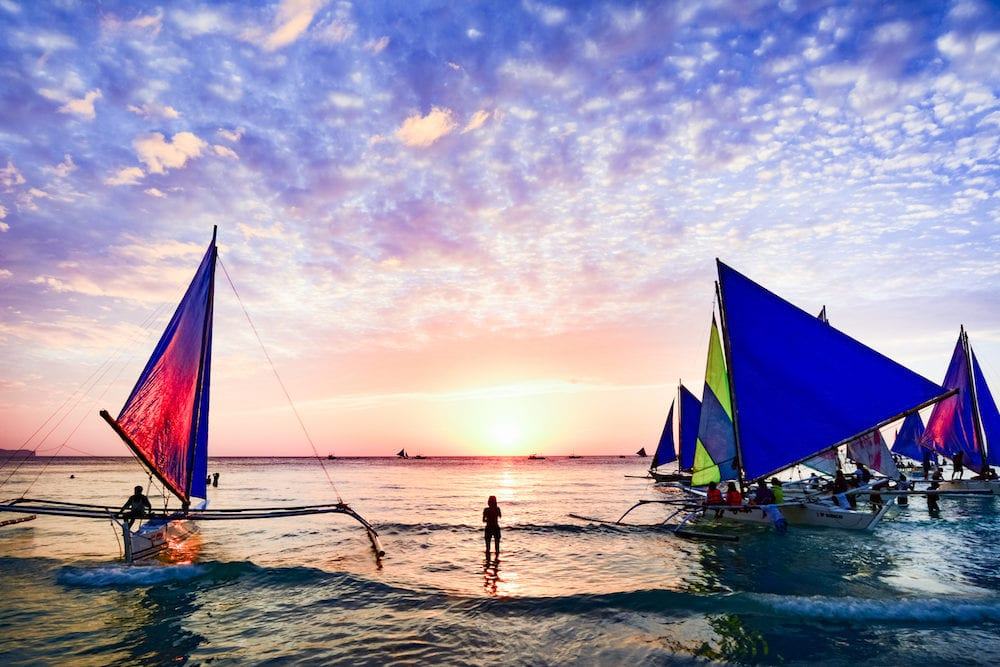 BORACAY PHILIPPINES - Several tourists are enjoying the spectacular sunset on the island of Boracay seated on typical Philippines boats.