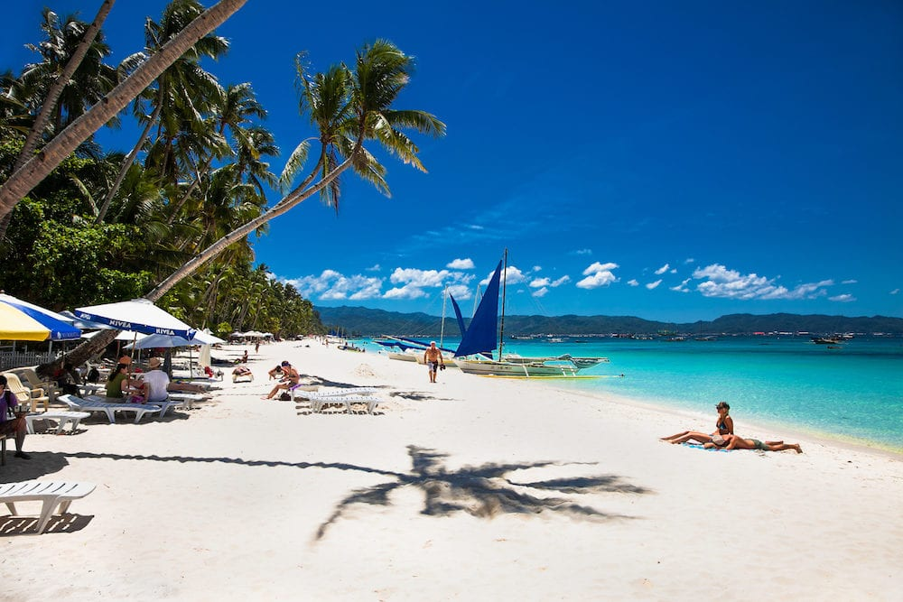 BORACAY, PHILIPHINES- Tropical vacation on white sand beach with sun, blue sky and palm trees. White beach at Boracay island Philiphines.