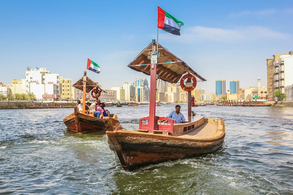 Dubai, United Arab Emirates -Traditional Abra ferries along Dubai Creek. The Creek divides the city into two main sections: Deira and Bur Dubai. On background, Twin Towers, old downtown.