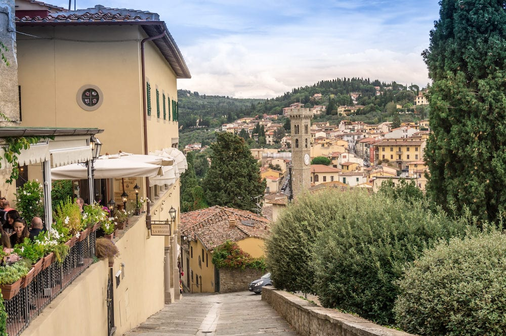 Fiesole Florence Italy. View of people dine in the restaurant and Fiesole town center with cathedral tower in the background