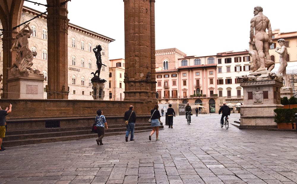 FLORENCE, ITALY - People in Piazza della Signoria in Florence; Early morning on Piazza della Signoria in front of the Palazzo Vecchio in Florence; the main point of the origin and history of the Florentine Republic.