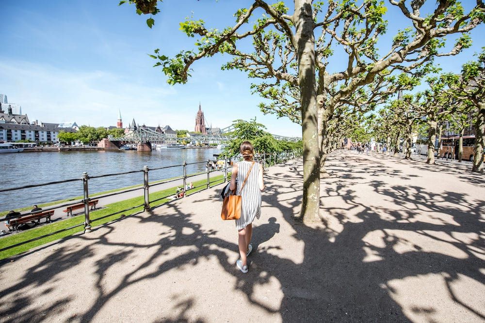 Young woman walking outdoors in the park near the river in Frankfurt