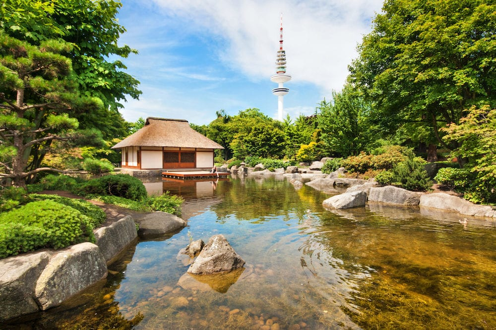 Beautiful view of Japanese Garden in Planten um Blomen park with famous Heinrich-Hertz-Turm radio telecommunication tower in the background Hamburg Germany
