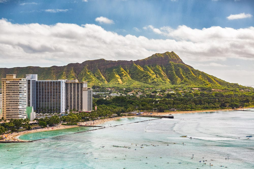 Hawaii vacation travel aerial view of Waikiki beach and Honolulu city with Diamond Head mountain in background. Urban landscape for USA travel summer vacation destination.