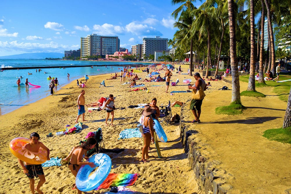 Waikiki Beach in Honolulu, HI: Popular crowded beach surrounded by palm trees, highrise hotels, and the ocean taken in Waikiki Beach, HI where tourists can stay at a hotel on the beach and relax at the beach during the day
