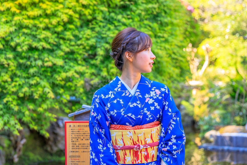 Kamakura, Japan -Take-Dera Temple garden in Kamakura with one single woman in classical Japanese kimono on green springtime season foliage background. Japanese experience and lifestyle