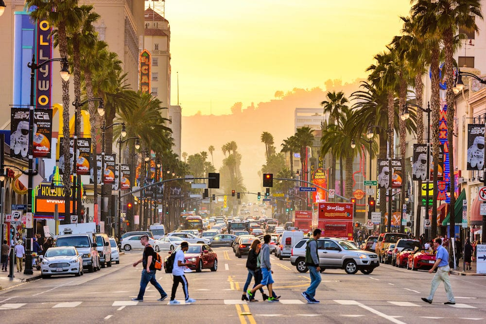 LOS ANGELES, CALIFORNIA -Traffic and pedestrians on Hollywood Boulevard at dusk. The theater district is famous tourist attraction.