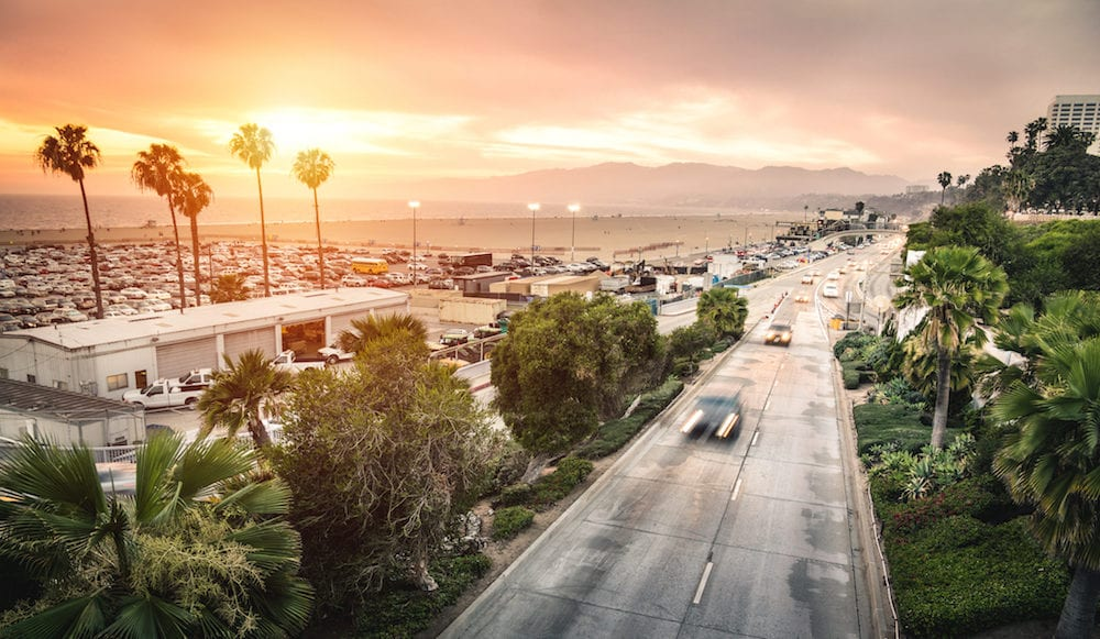 Aerial panoramic view of Ocean Ave freeway in Santa Monica beach at sunset - City streets of Los Angeles and California state surrounds - Warm twilight color filter tones with dark vignetting