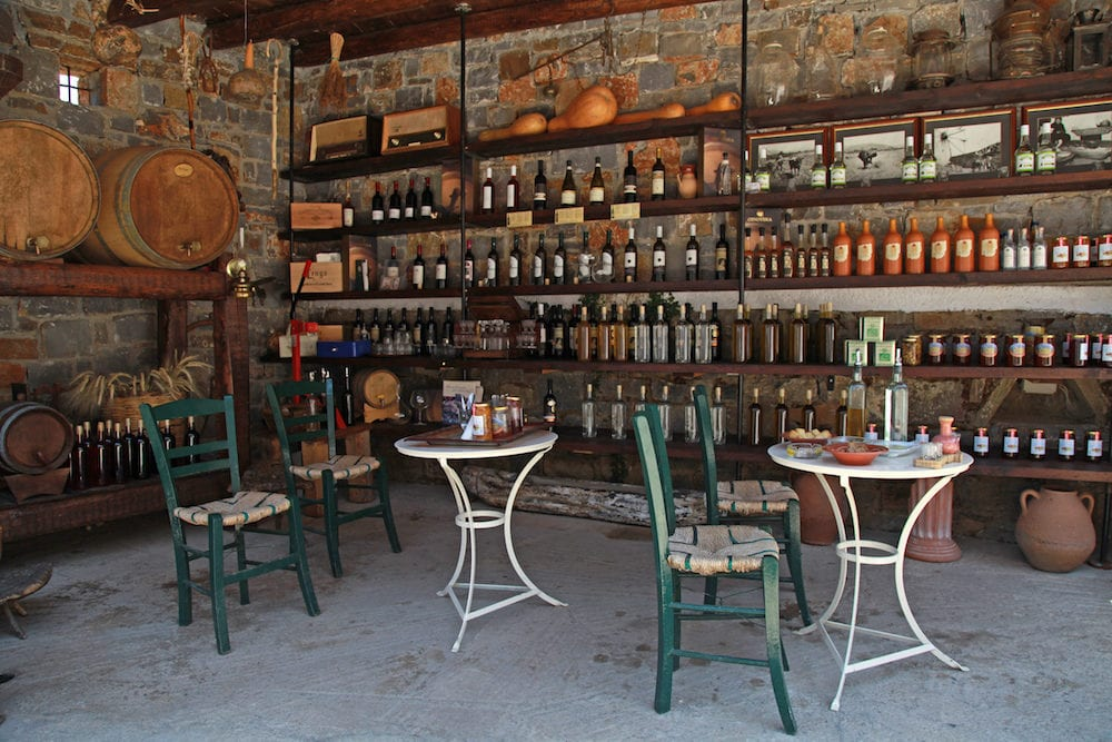 LASSITHI, GREECE -Interior with wine barrels and bottles in the old cellar of a winery Lassithi, Crete, Greece.
