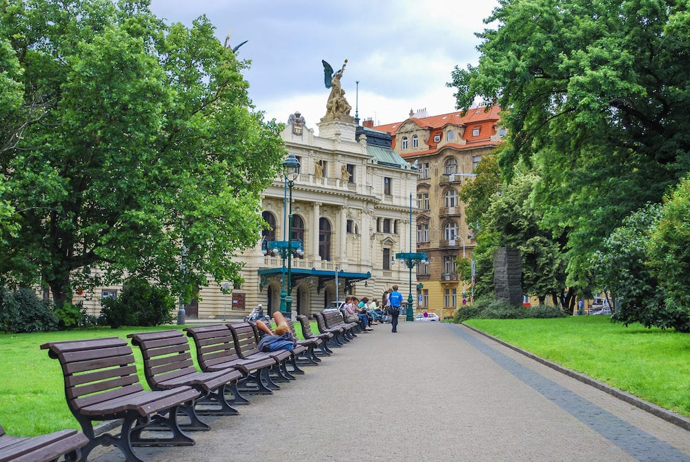 PRAGUE, CZECH REPUBLIC - Green park alley with benches with the view of Vinohrady Theatre (Dramatic Theater), people rest on benches
