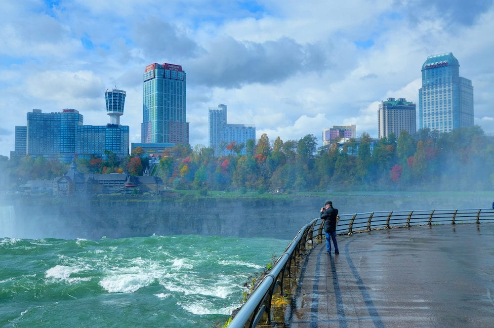View on Niagara fall waterfall of Buffalo city a man and Toronto city Canada. Green blue water. Best famous Niagara sightseeing tours holidays vacations travel