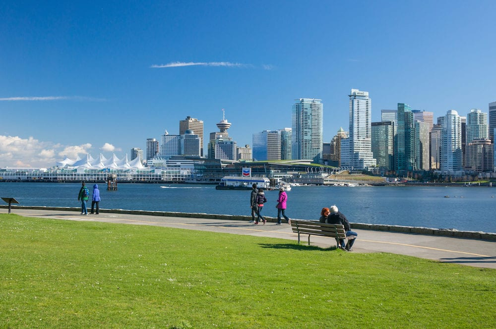 VANCOUVER CANADA - Unidentified people walk on seawall in Stanley Park. Seawall is 8.8-kilometre paved route that loops around the park. It's one of the park biggest attractions for sightseers and recreation enthusiasts.