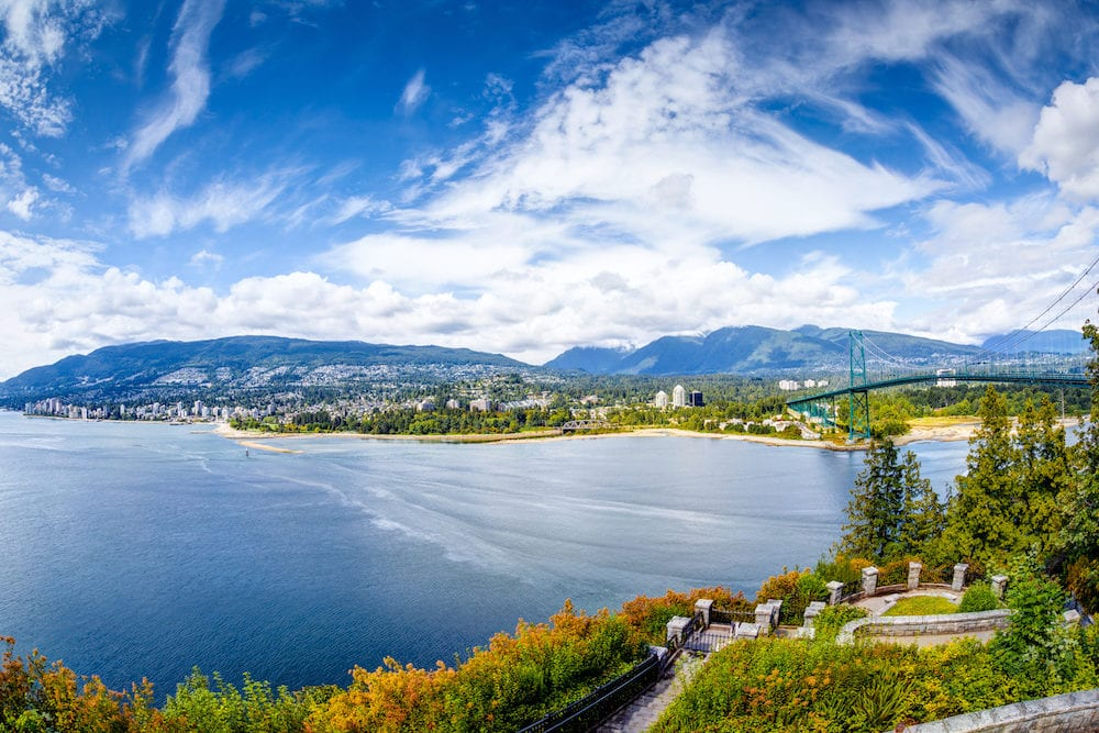Vancouver skyline panorama taken at Prospect Point Stanley Park showing Lions Gate Bridge on right and West Vancouver on the left. Prospect Point is located on the south side of the First Narrows of Burrard Inlet