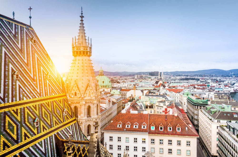 Aerial view over the historical rooftops of Vienna from the north tower of famous St. Stephen's Cathedral in beautiful golden evening light at sunset in summer central Vienna Austria