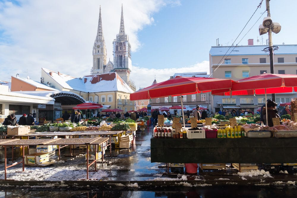 Zagreb Croatia: Stand with red parasols and visitors at Dolac market during wintertime with snow and cathedral in the background