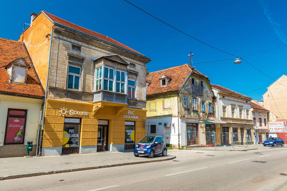 Karlovac - Croatia: View of the old houses on the street of Karlovac. Small blue car parked on a pavement