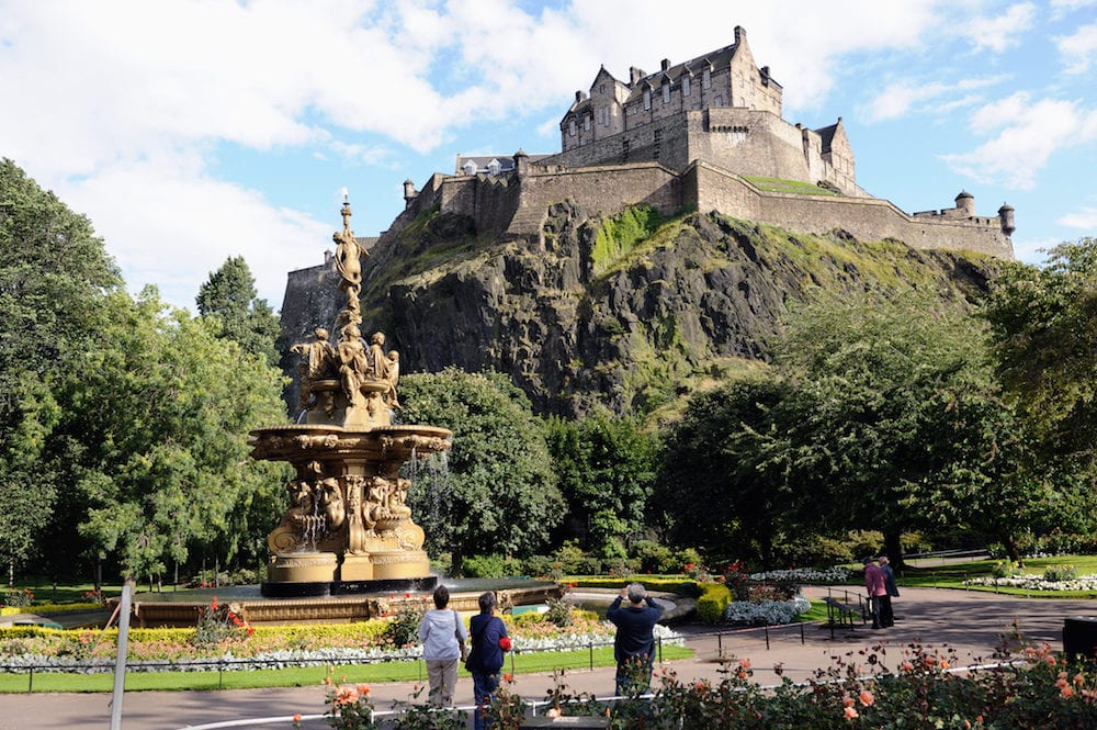 Edinburgh Castle Scotland UK from the West Princes Street Gardens with the Ross Fountain in the foreground in the late afternoon after rain has cleared the air.