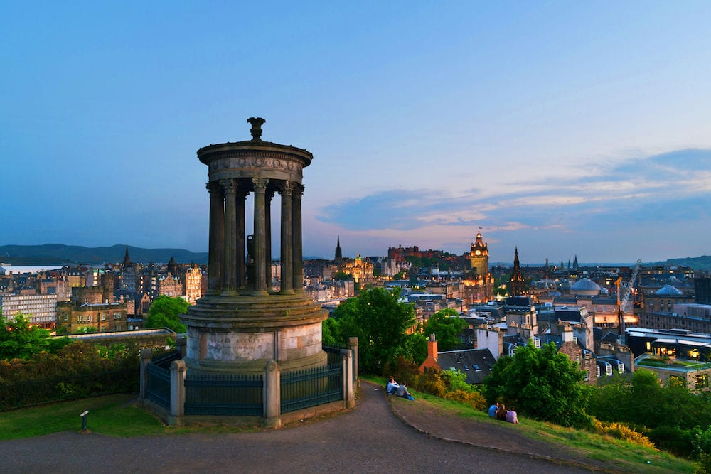 Edinburgh, Scotland. Calton Hill in Edinburgh, Scotland, UK. Aerial view of the city with Castle and Clock Tower in the evening. Sunset cloudy sky and illuminated landmarks