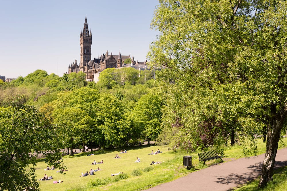 Glasgow Scotland UK: - Young people, students of the University of Glasgow enjoying a warm sunny day on the lawns of Kelvingrove park, the University in the background