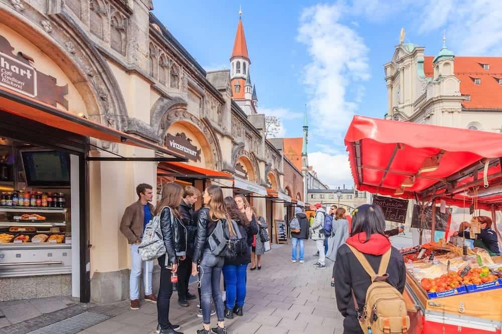 MUNICH BAVARIA GERMANY Pedestrians browse shops and stalls beneath St. Peter's Church Peterskirche along Viktualienmarkt market street in Munich Bavaria Germany.