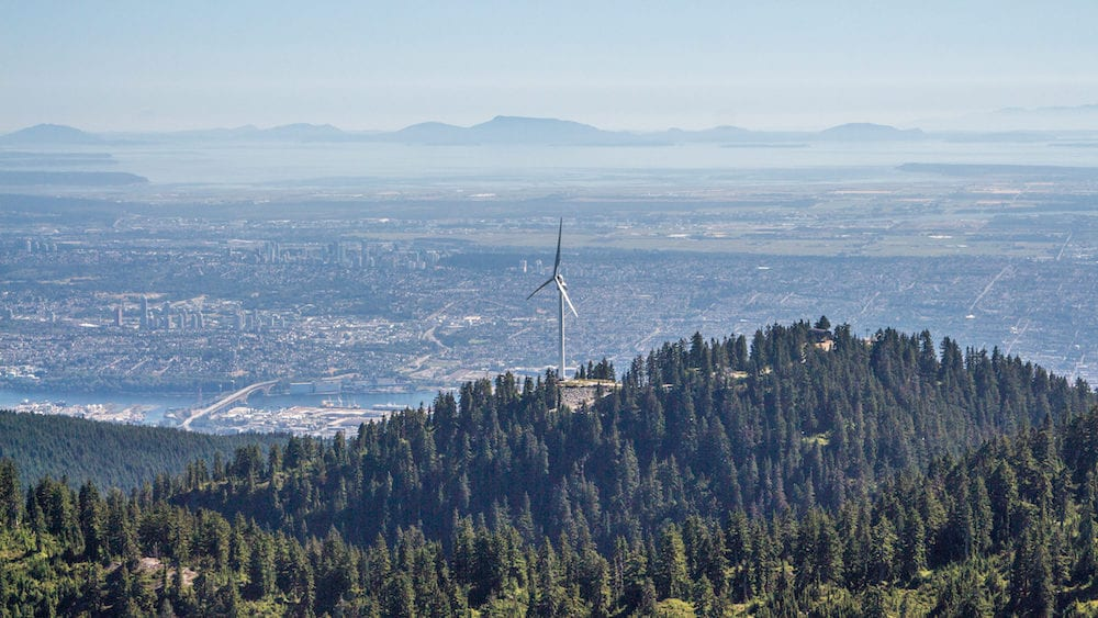 View from the helicopter on Vancouver downtown at the bottom of Grouse Mountain peak with the Eye Of The Wind among the green forest.