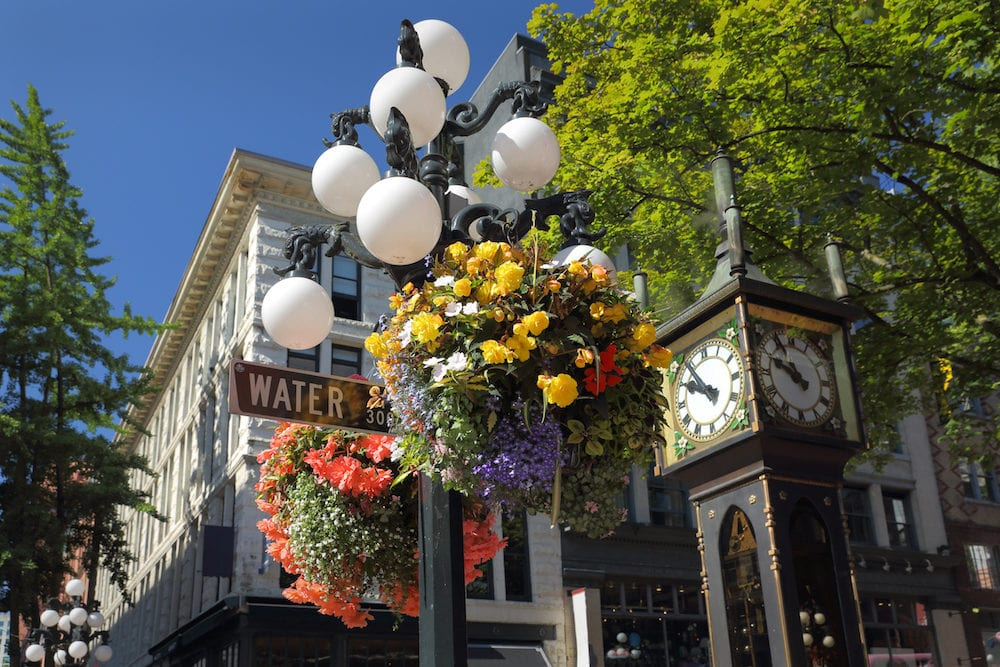 A heritage street lamp and hanging basket next to the steam clock in the heart of Vancouver's historic Gastown. British Columbia, Canada.