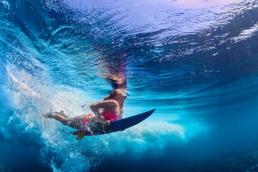 Young active girl wearing bikini in action - surfer with surf board dive underwater under big ocean wave. Family lifestyle people water sport adventure camp and beach extreme swim on summer vacation.