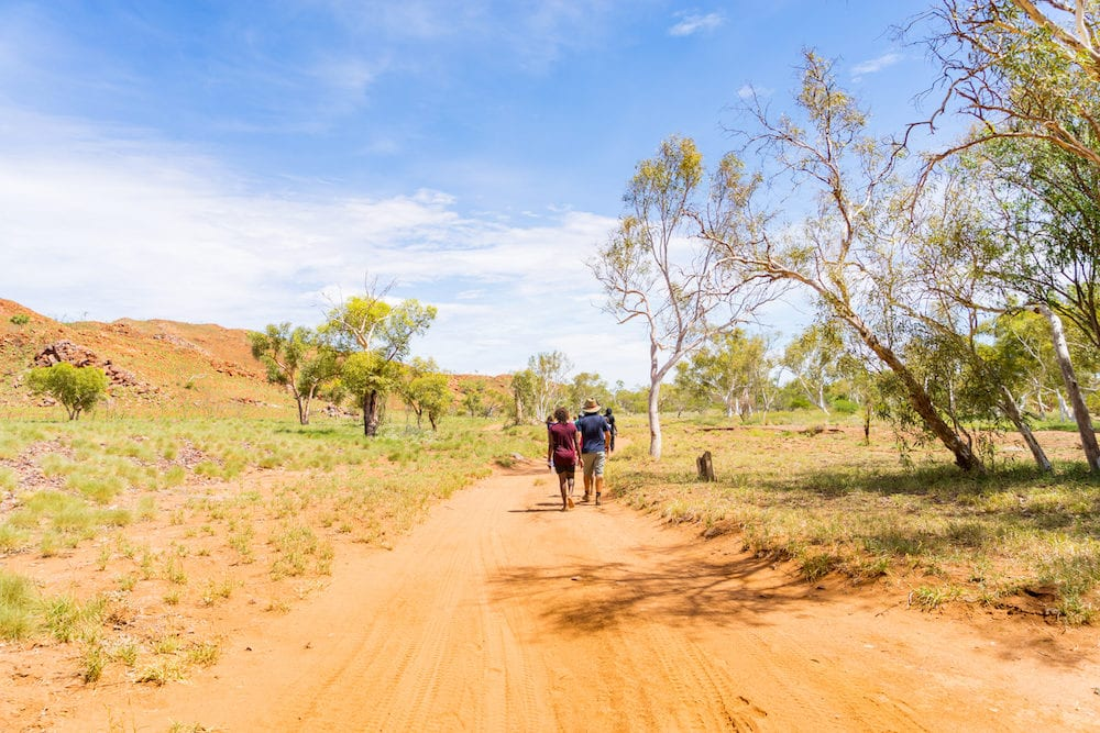 People hiking on a hot day along a track in the Pilbara region in North Western Australia, Australia.
